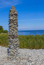 High stone tower next to sea, made from people Royalty Free Stock Photo