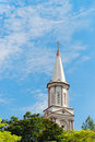 High tower turret of the church under blue sky in green trees Royalty Free Stock Photo