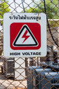 High voltage danger sign at fence to warning about dangerous from electricity Royalty Free Stock Photo