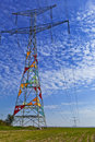 High voltage electric pole standing in a field Royalty Free Stock Image