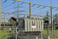 High voltage electric substation transformer in switch field with cables and electricity pylon Royalty Free Stock Photography