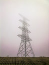 High voltage electricity pylon in the morning mist. Royalty Free Stock Photo