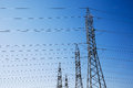 High voltage industrial pylons for electricity distribution row of numerous heavy duty parallel wires on a blue sky background Royalty Free Stock Images