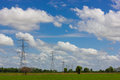 High voltage pole with green fields. Royalty Free Stock Photo