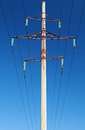 High voltage power lines and pylon above clear blue sky Stock Image