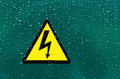 High voltage symbol on a green background with raindrops Stock Photography