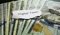 Higher taxes note on assorted cash Royalty Free Stock Photography