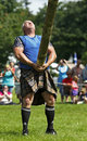 Highland games caber toss athlete dirk bishop tosses the at the new brunswick festival july in fredericton canada Royalty Free Stock Image