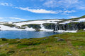 Highland norwegian summer landscape with lake and snow waterfall Royalty Free Stock Image