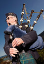Highlander wearing kilt and playing bagpipes Stock Images