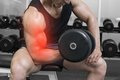 Highlighted arm of strong man lifting weights Royalty Free Stock Photo