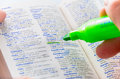 Highlighting the handicap word on a dictionary close up of man hands using florescent green marker to highlight Royalty Free Stock Image