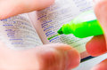 Highlighting the privacy word on a dictionary close up of man hands using florescent green marker to highlight Stock Photo