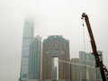 Highrise buildings- skyscraper and construction crane in foggy weather Royalty Free Stock Photo