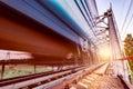 Highspeed train moves fast on the bridge at sunsset Stock Photos