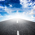 Highway asphalted over blue sky with white clouds background Royalty Free Stock Image