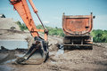 Highway construction site details with excavator bucket and dumper truck Royalty Free Stock Photo