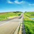 Highway in hilly terrain and blue sky Royalty Free Stock Images