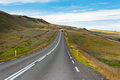 Highway through Icelandic landscape under a blue summer sky. Royalty Free Stock Photo