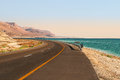 Highway runs along dead sea and red mountains in the desert in israel Stock Images