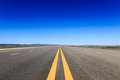 Highway in steppe against a blue sky Royalty Free Stock Photo
