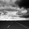 Highway and storm clouds empty dark bw image Stock Images
