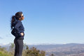 Hike to the top woman stops hiking and admires viewpoint on of mountain Royalty Free Stock Photo