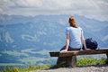 Hiker and alpine mountain view recreational rests on a bench with a over hills in bavaria germany Royalty Free Stock Photos