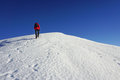 Hiker ascending a snow slope in winter Royalty Free Stock Image