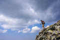 Hiker with backpack descending from the top of the mountain dramatic clouds Stock Image