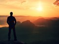 Hiker in black  stand on the peak in rock empires park and watching over the misty and foggy morning valley to Sun. Beautiful mome Royalty Free Stock Photo