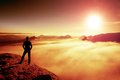 Hiker in black stands on rock abve valley within daybreak and watch to sun beautiful moment the miracle of nature man hot Stock Image