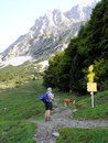Hiker at a crossroads in the mountains and in the background the steep rocks of the kaiser mountains in tyrol austria Stock Images