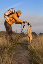 Hiker and dog female has break on her walk feeds her Stock Photography