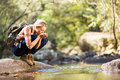Hiker drinking water young stream in mountain Royalty Free Stock Photo