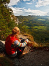 Hiker enjoying the view sitting on edge of a cliff looking into a valley Stock Photos