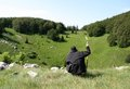 Hiker enjoying the view trekker dressed in black taking a break contemplating beautifil of field and meadows in croatian mountain Stock Photo