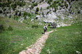 Hiker exploring a walking down a path towards a mountain Stock Photography