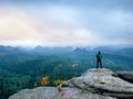 Hiker in green windcheater, cap and dark trekking trousers stand on mountain peak rock. Royalty Free Stock Photo
