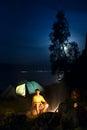 A hiker at his camp at night