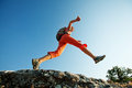 Hiker jumps over the rock Royalty Free Stock Images