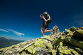 Hiker jumps over stones in mountains Royalty Free Stock Image