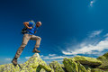 Hiker jumps over stones in mountains Stock Photography