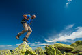 Hiker jumps over stones in mountains Stock Images