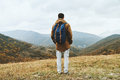 Hiker man enjoying by scenics in autumn season with backpack full length standing among mountains and Royalty Free Stock Photography