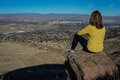 Hiker overlooking reno nevada woman sitting on boulder the city of on a sunny day Stock Photos