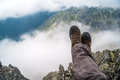 Hiker resting high in the mountains hiking boots of a while taking a rest over clouds Stock Photography