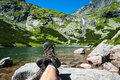 Hiker resting over the glacier lake and waterfall with a in background in high mountains Stock Photos