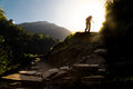 Hiker in silhouette hiking at highland towards sunrise.  Lens flare intended Royalty Free Stock Photo