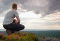 Hiker in squatting position on a rock in heather bushes enjoy the cloudy scenery Stock Photo